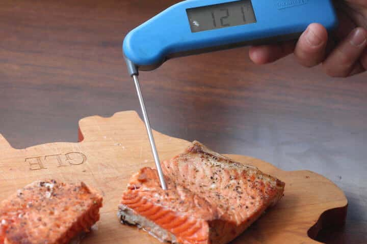 Meat thermometer checking salmon fillet temperature at 121 degrees Fahrenheit