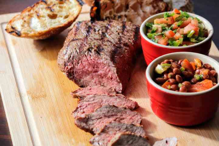 Grilled tri tip thinly sliced showing a nice pink interior on a cutting board with Santa Maria salsa and pinquito beans and crusty bread