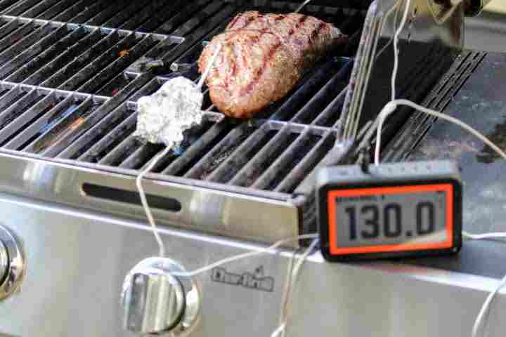 Monitoring a tri tip roast on the grill using a WiFi meat thermometer , revealing an internal temperature of 130 degrees Fahrenheit.