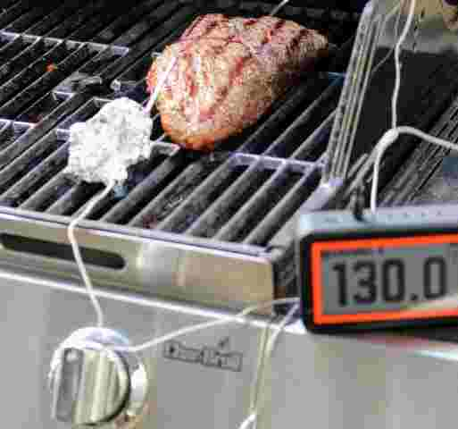 Tri tip on the cool side of the grill registering an internal temperature of 130 degrees Fahrenheit, ready to pull off the grill