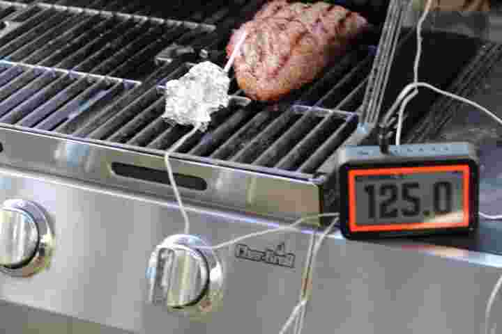 Monitoring a tri tip roast on the grill using a WiFi meat thermometer , revealing an internal temperature of 125 degrees Fahrenheit.