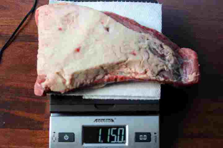 An untrimmed tri tip weighing 1 pound 15 ounces on a scale.