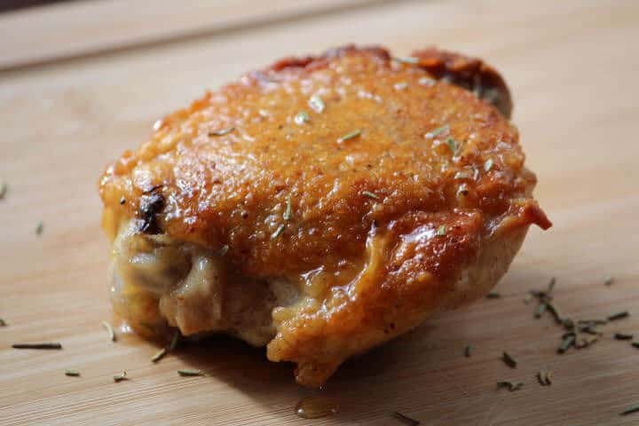 Bone-in chicken thigh with crispy skin resting on cutting board