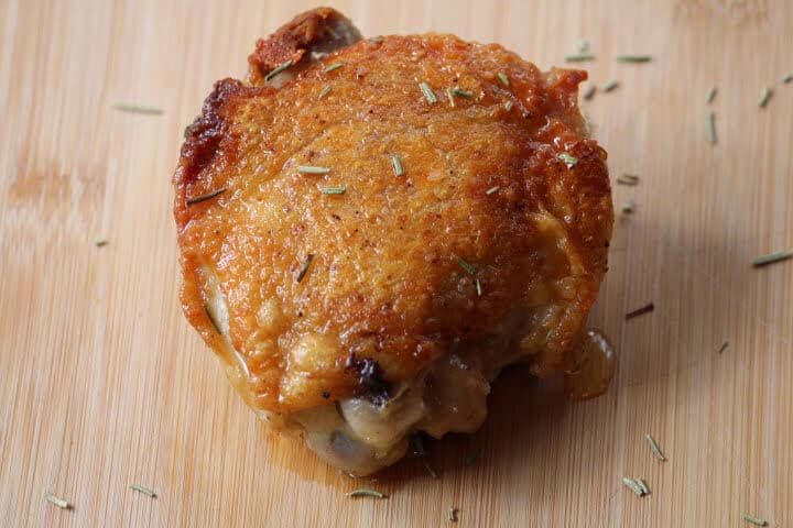 Chicken thigh with a crispy, golden-brown skin on a cutting board