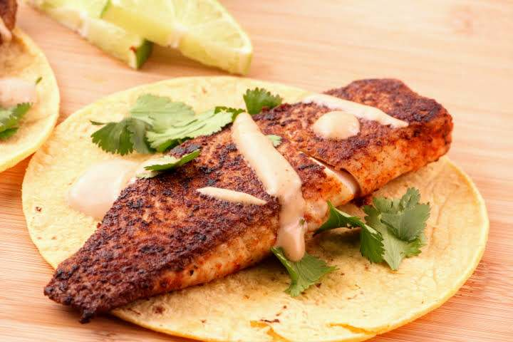 A pan-fried tilapia fillet on a corn tortilla topped with chipotle crema