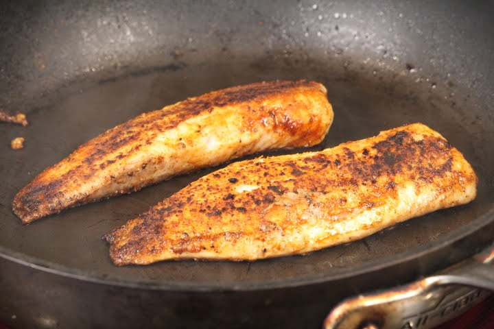 Tilapia fillets frying in a pan