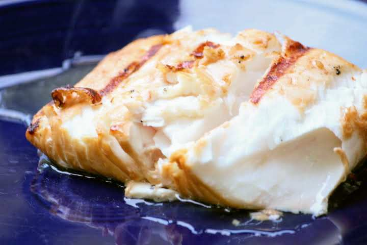 A halibut fillet grilled to 124 degrees Fahrenheit resting on a plate with a portion of it flaked off revealing a juicy interior