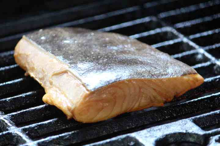 A halibut fillet on the grill flesh side down against the grain of the fish