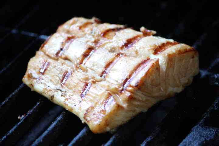 A halibut fillet with grill marks perpendicular to the grain of the fish