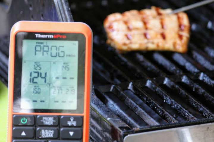 A halibut fillet measuring an internal temperature of 124 degrees Fahrenheit on a gas grill