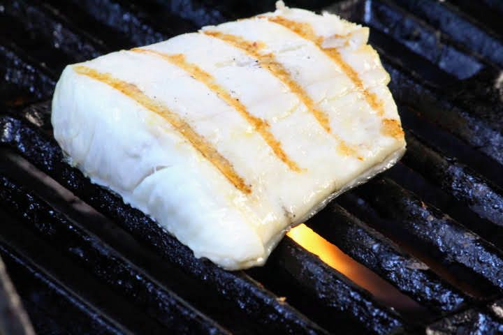 A halibut fillet on the grill with grill marks