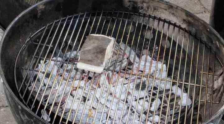 A halibut fillet over hot coals on a charcoal grill