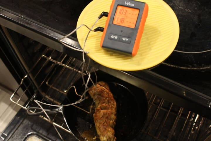 Checking the temperature of pork tenderloin with an oven-safe digital meat thermometer