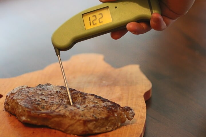 Checking the temperature of rare steak at 122 degrees Fahrenheit