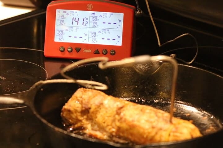 Pork tenderloin registering 141 degrees Fahrenheit with an oven-safe digital meat thermometer