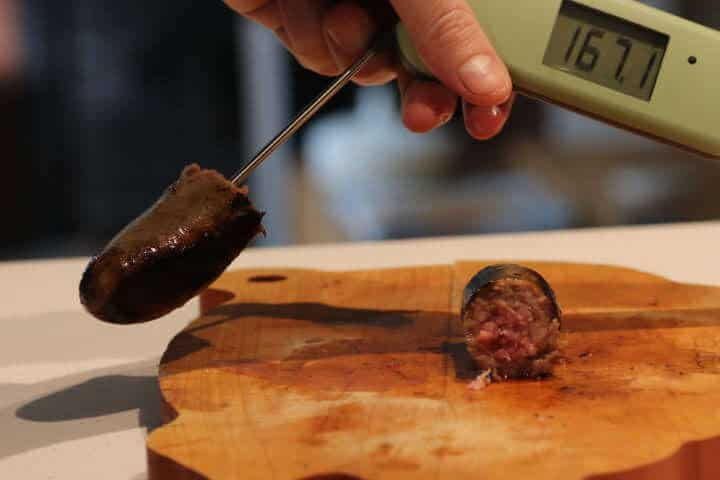 A bratwurst temping at 167 degrees Fahrenheit while having a pink middle at the same time.