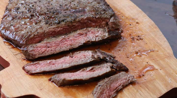 Flank steak sliced across the grain into pieces on a wooden cutting board