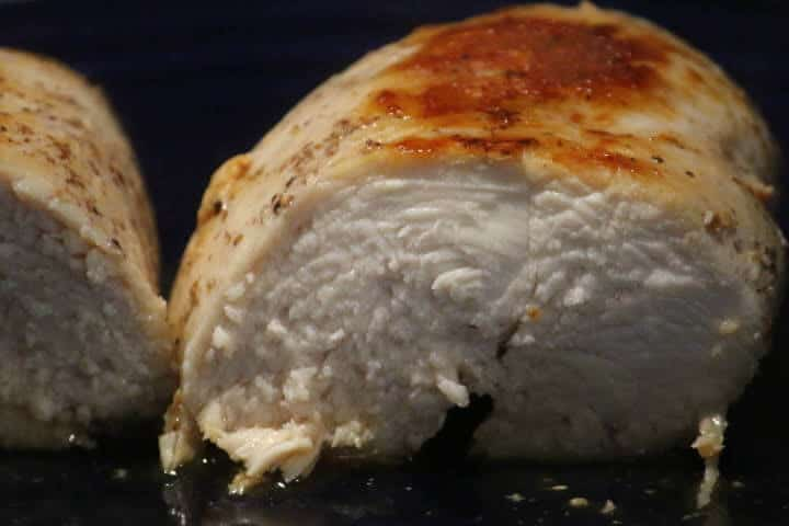 Chicken breast cut in half revealing a white middle that's done