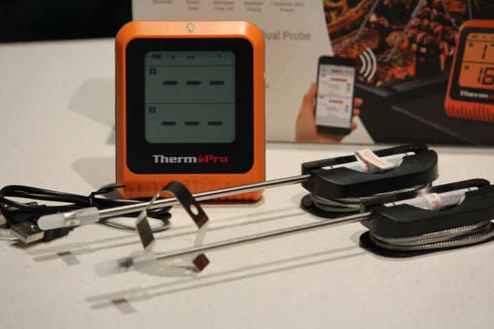 ThermoPro TP-25H2 Bluetooth meat thermometer with its two probes, a grate clip, and a USB cord for charging