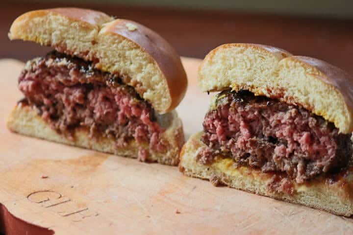 A hamburger cut in half, revealing pinkness in the meat even though it was cooked to 152 degrees Fahrenheit.