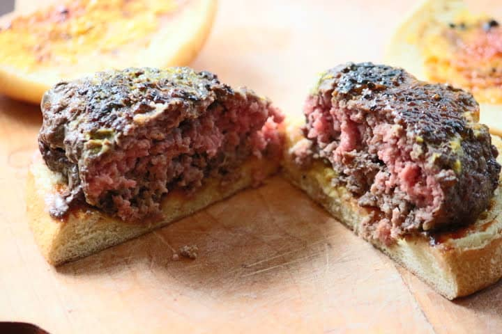 Hamburger cooked to an internal temperature of 152 degrees Fahrenheit still showing plenty of pink color in the middle.