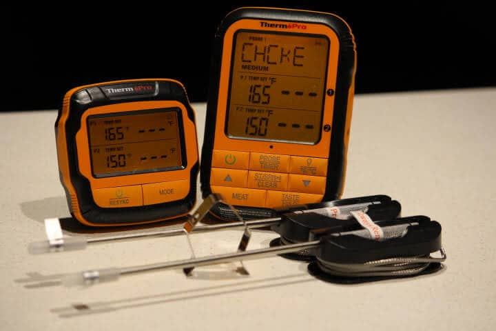 The ThermoPro TP28 Dual Probe Remote Meat Thermometer''s receiver on the left, transmitter on the right with its two probes in front with a grate clip