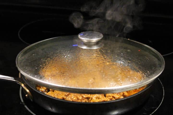 Ground chorizo sausage crumbles cooking in a pan with a lid on the stovetop
