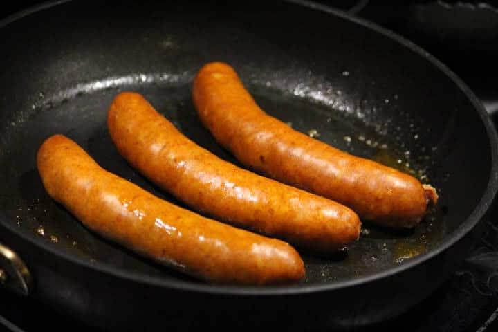 Searing chorizo sausage links in a pan