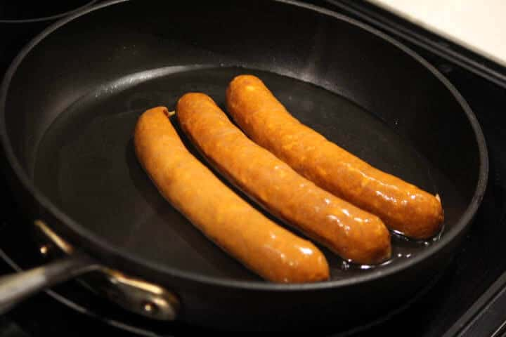 Three link chorizo sausages in a pan on a stovetop with just enough water to cover the bottom of the pan