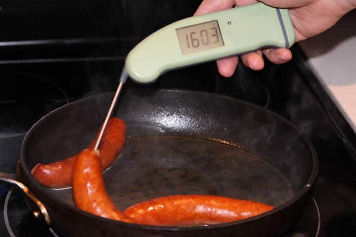 A chorizo sausage link in a pan of simmering water measuring 160 degrees Fahrenheit on an instant-read meat thermometer