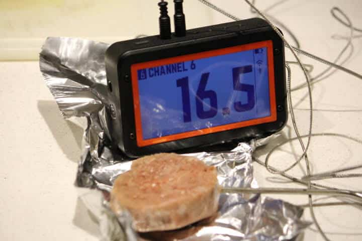 A frozen turkey sausage patty registering an internal temperature of 16.5 degrees Fahrenheit on a probe thermometer.