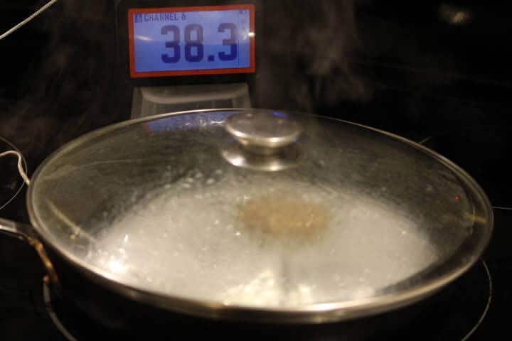 A frozen turkey sausage patty cooking in a covered pan on the stovetop.