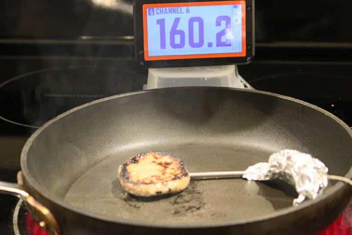 Pork breakfast sausage patty in a pan measuring 160 degrees Fahrenheit on a probe meat thermometer