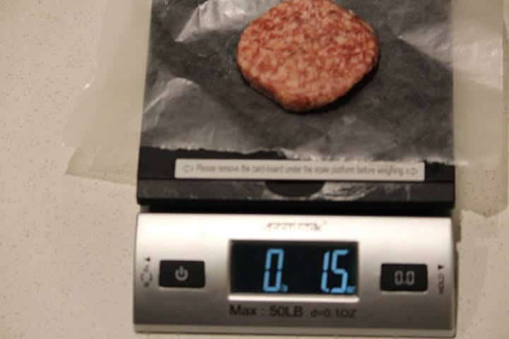 A pork sausage patty measuring a weight of 1.5 ounces on a food scale.
