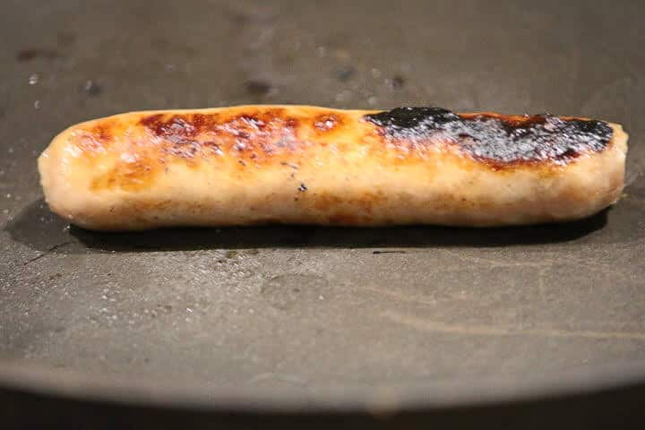 Breakfast sausage link with a well-browned exterior.