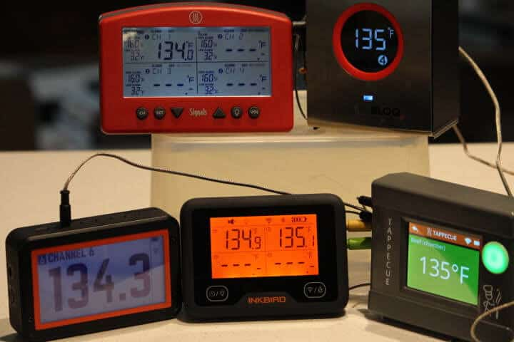 (Clockwise from the top) The Thermoworks Signals, SmokeBloq, Tappecue Touch, Inkbird IBBQ-4W, and Fireboard 2 Drive WiFi meat thermometers measuring a sous vide water bath at 135 degrees Fahrenheit