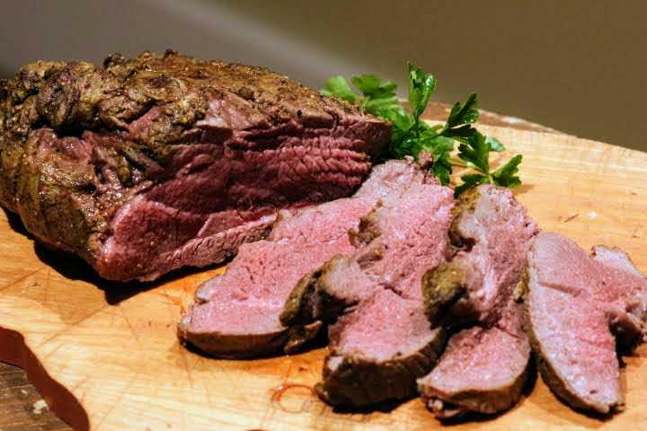 Leg of lamb sliced on a cutting board