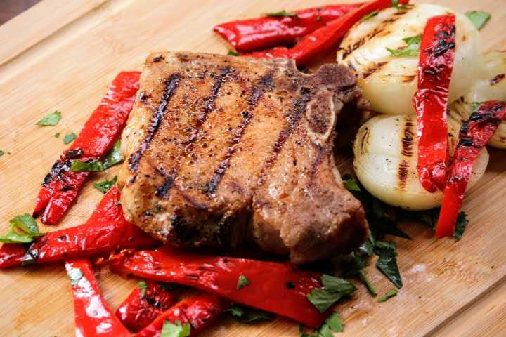 Pork Chop with visible grill marks resting on peppers and onions