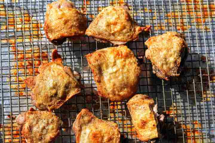 Chicken thighs with crispy skin on a baking sheet with wire rack after cooking for 40 minutes in a 425 degree oven