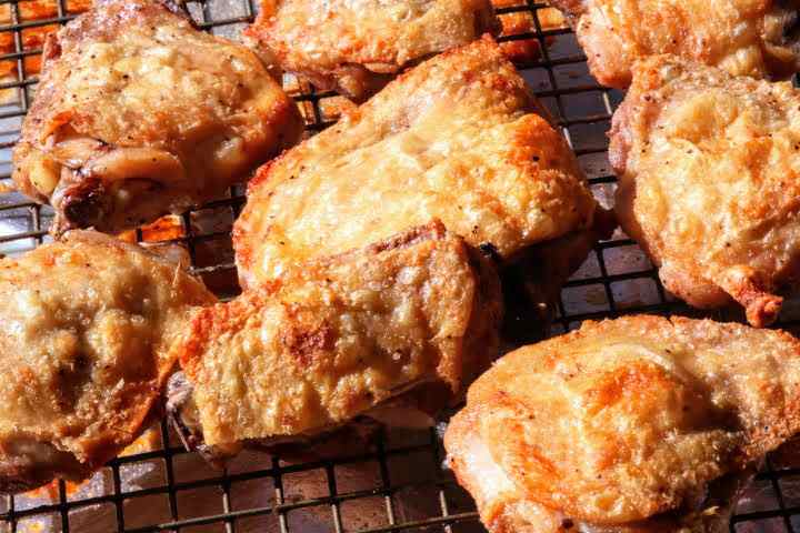 Baked Chicken Thighs on a wire rack on a cooking sheet revealing ultra-crispy skin