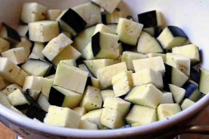 Cubes of eggplant sprinkled with salt in a colander