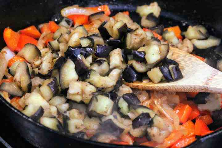 Adding eggplant to red peppers and onions in a cast iron skillet