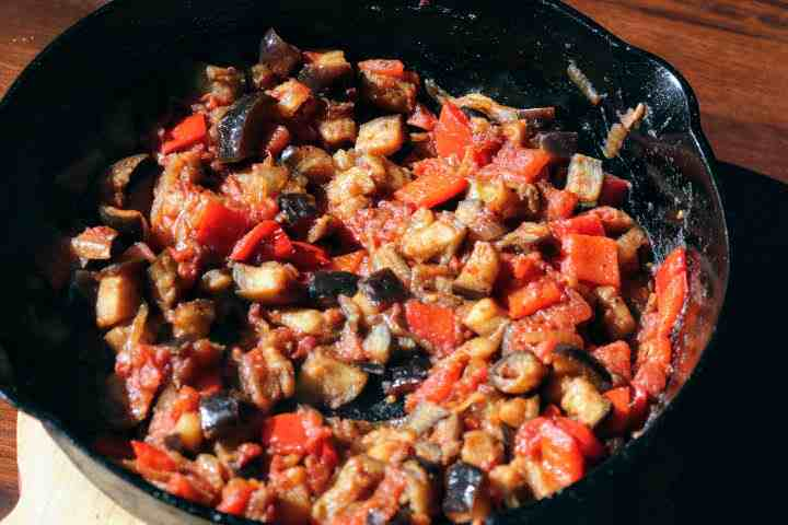 A samfaina of eggplant, red pepper, onions and tomatoes in a cast iron skillet.