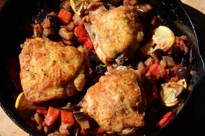 Three chicken thighs with fried chicken-like skin in a pan with vegetables