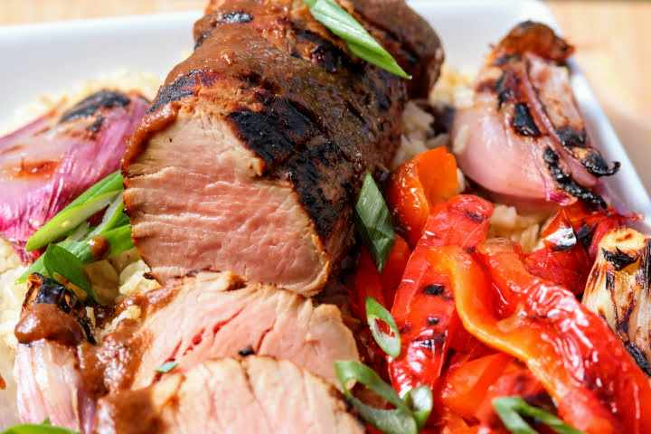 A charcoal grilled pork tenderloin with soy honey sesame glaze on a bed of brown rice with grilled red peppers and shallots