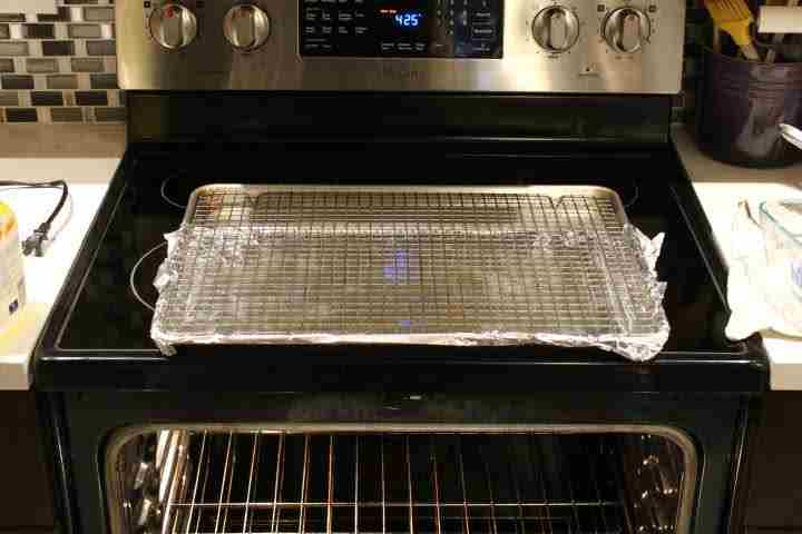 Oven preheating to 425 degree Fahrenheit with a baking seet lined with aluminum foil with a wire rack insert resting on the stovetop and the oven rack set to middle position
