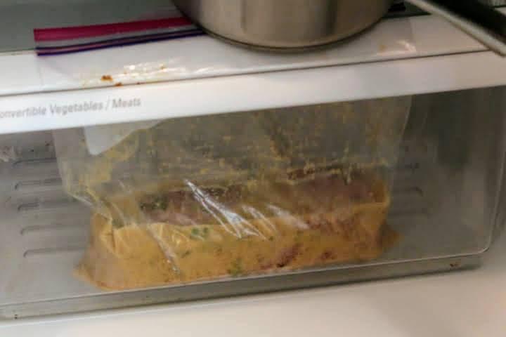 Pork tenderloin marinating in a zip lock freezer bag in refrigerator