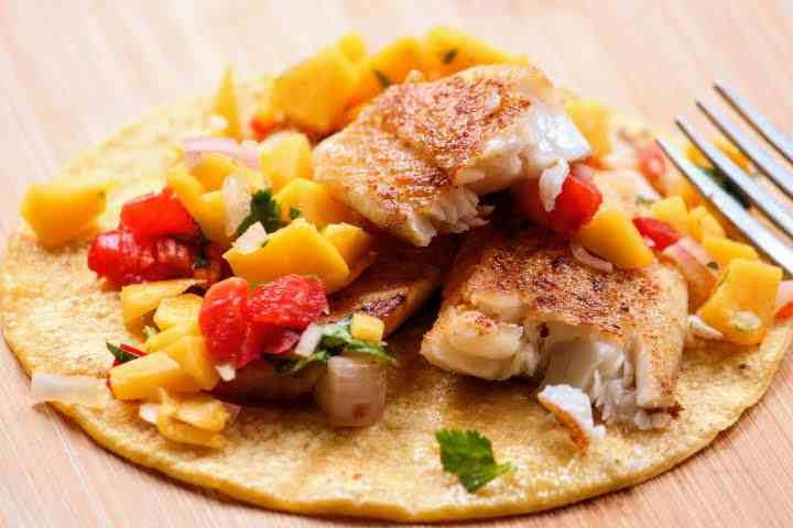 Pan-fried Tilapia fillet cut into chunks revealing a moist interior on top of a corn torilla with mango salsa