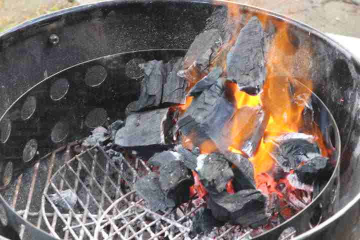 A pile of lump charcoal on fire on one side of a charcoal grill creating a two-zone fire