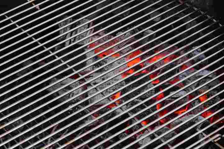 Charcoal that is glowing red hot with white ash underrneath a cooking grate on a grill